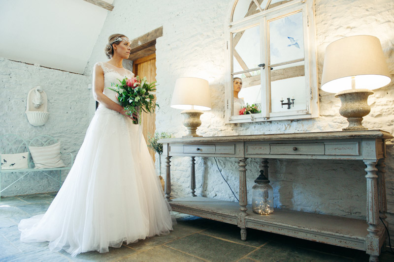 Bride looking in mirror in main entrance during a wedding at Stratton Court Barn