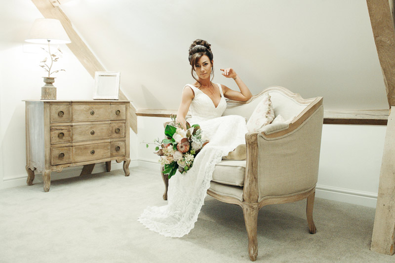 Bride on sofa holding wedding bouquet in wedding preparation room