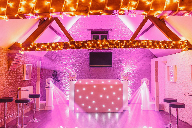 Weddings at Stratton Court Barn at night. Empty bar area with DJ set up complete with uplighters and fairy lights around beams