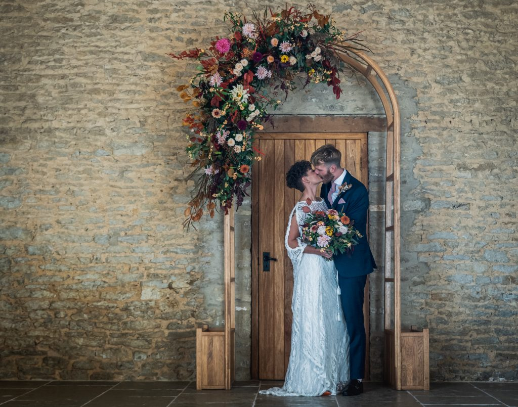 Bride and groom under flower arch after ceremony with covid restrictions